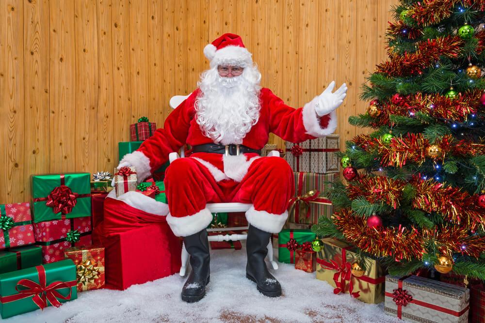 Papai Noel sentado na loja de calçados durante promoção de fim de ano natalino.