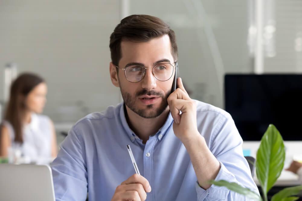 Homem fazendo ligação para cobrar cliente inadimplente.