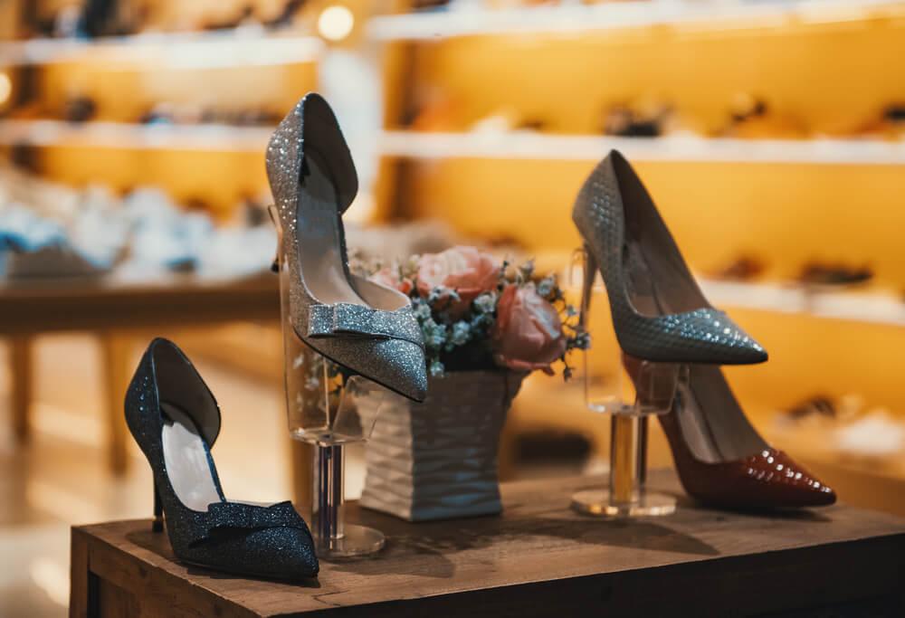 Vitrine da loja decorada com calçados e flores para o Dia da Mulher.