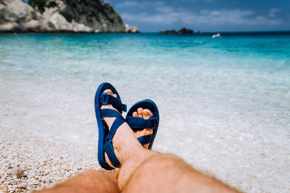 Pessoa com calçados de plástico na praia.