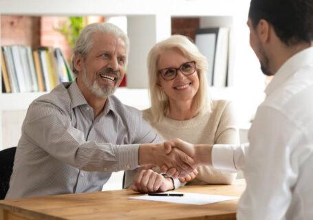 Vendedor apertando a mão de cliente, que está com sua esposa ao lado.