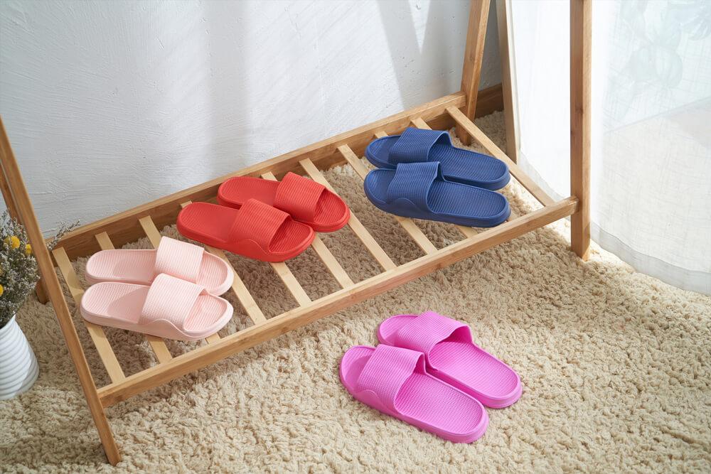 Calçados de plástico de tira larga em estante de madeira.
