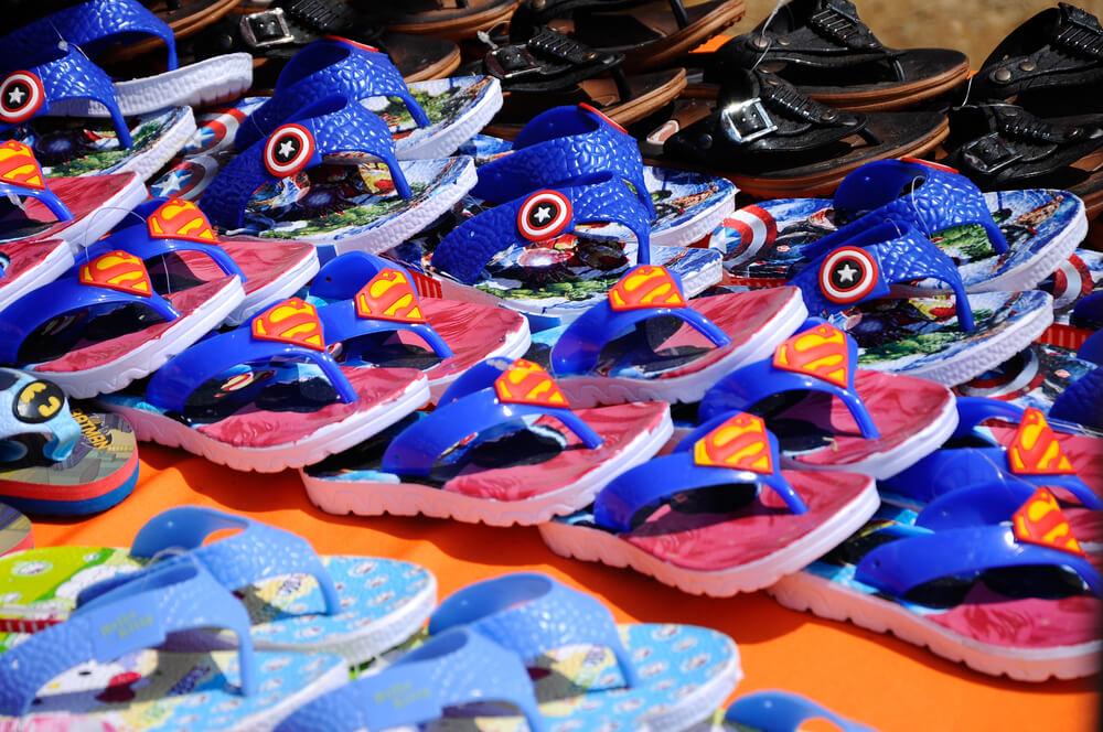 Calçados de plástico infantis de heróis enfileirados.