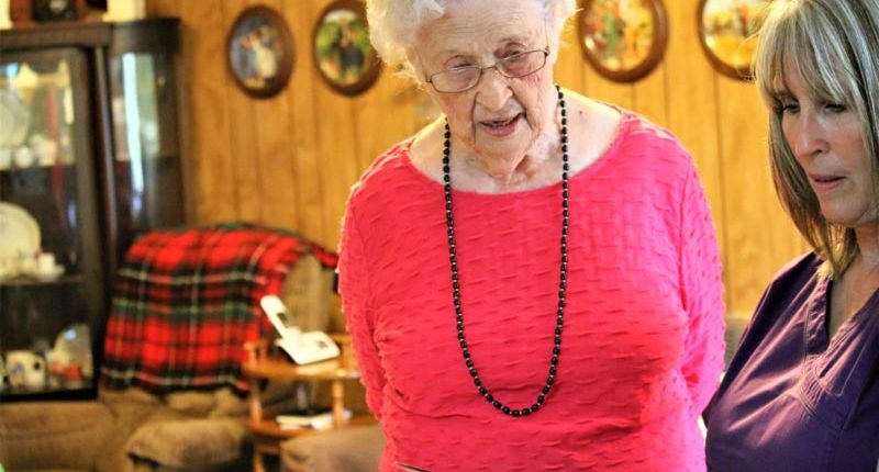 Nederland TX home care caregiver looking at photo album with senior client in hot pink
