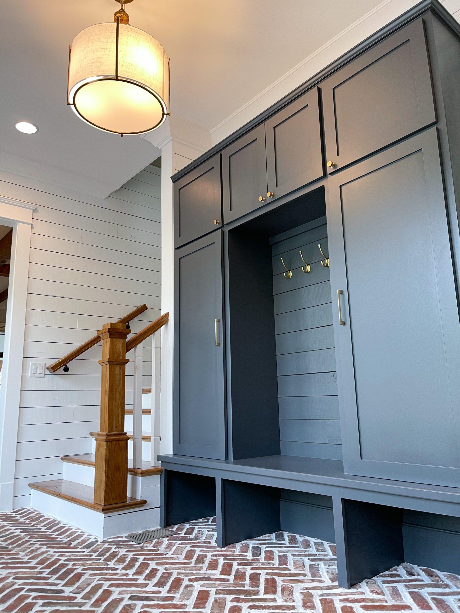 herringbone brick floors navy built-in cabinets white shiplap