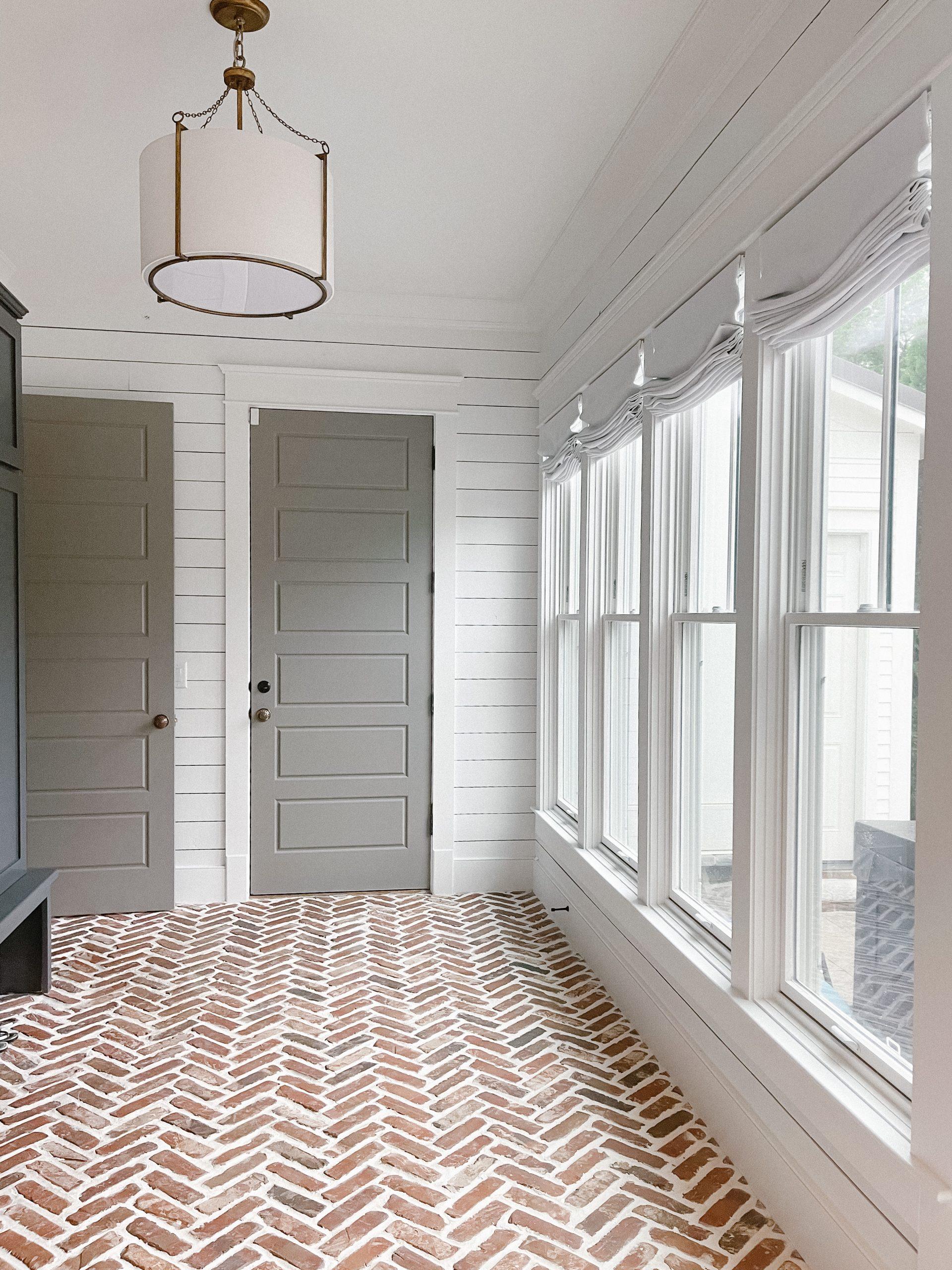 coastal mudroom makeover nashville, tn herringbone brick floors navy built-in cabinets white shiplap