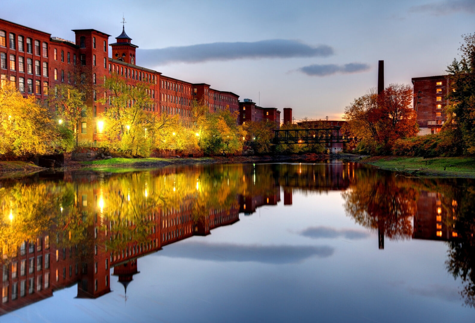 Nashua, New Hamshire industrial Mills refection along the banks of the Nashua River on a calm night. Nashua is the second largest city in the state of New Hampshire. Nashua is known for its  livability and economic expansion as part of the Boston region