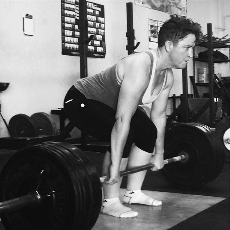 black and white photo of woman with hands on barbell in a deadlift position