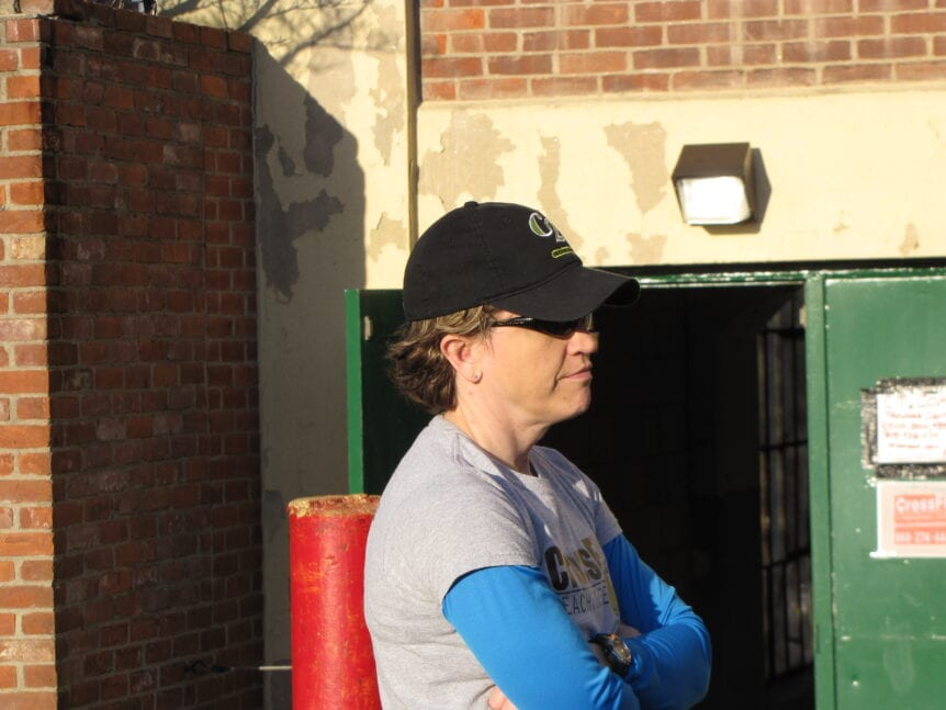 woman in baseball cap and sunglasses outside a brick building