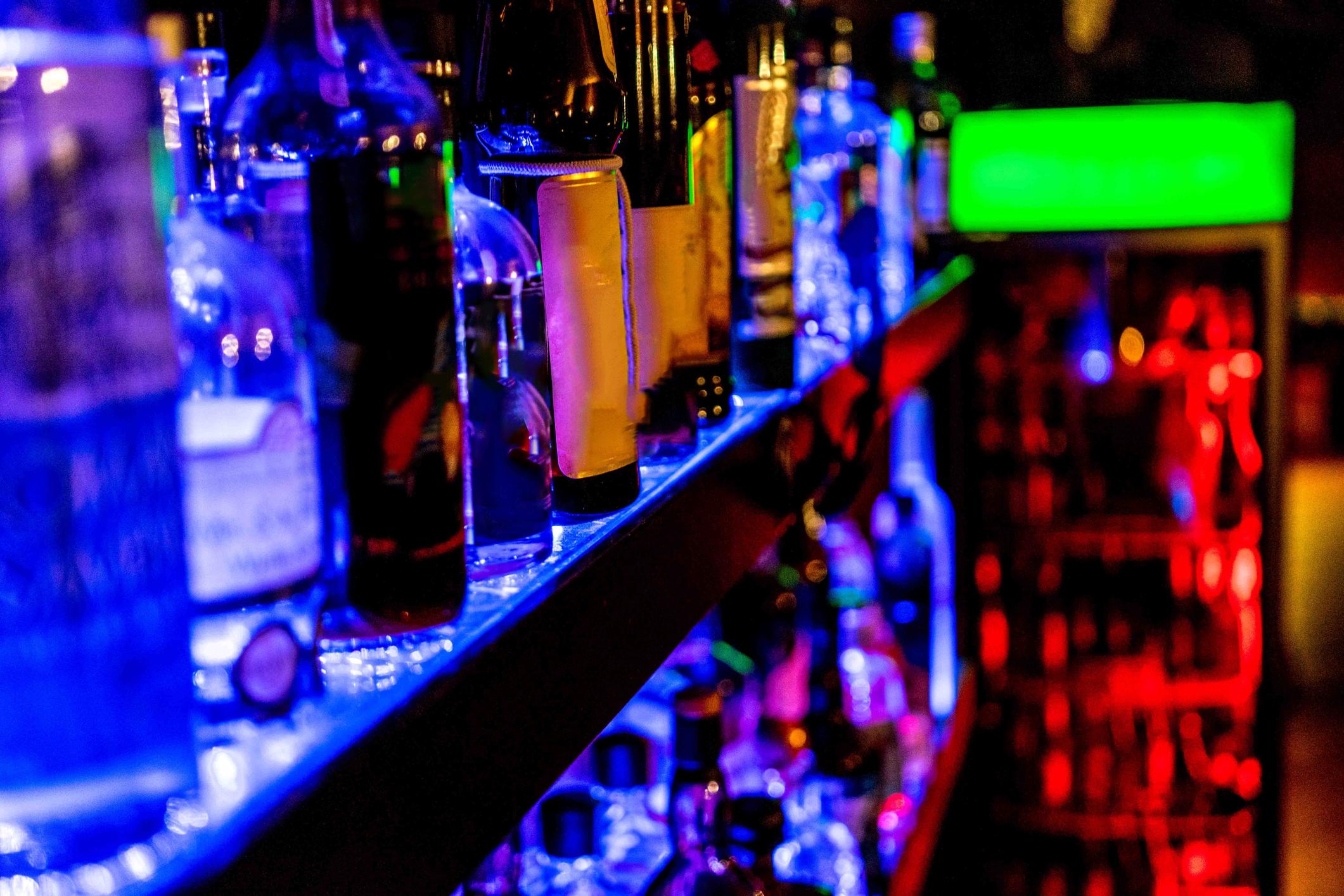 Bottles on a shelf, lightened up. spirituous beverages at a bar.