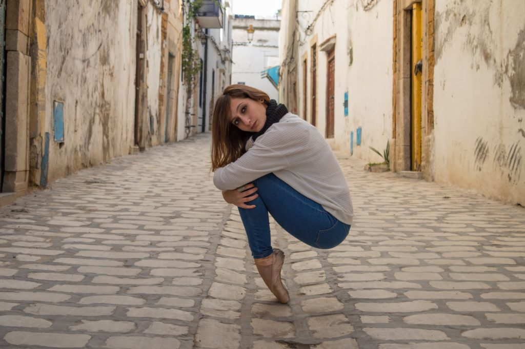 a person squatting with knees together, en pointe, on a cobblestone street