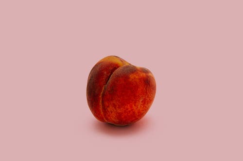 A peach on a pink background