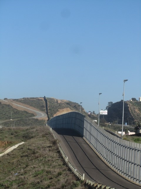 Picture of the border fence going east forever.  Don't cross the guard rail, you might go to jail.