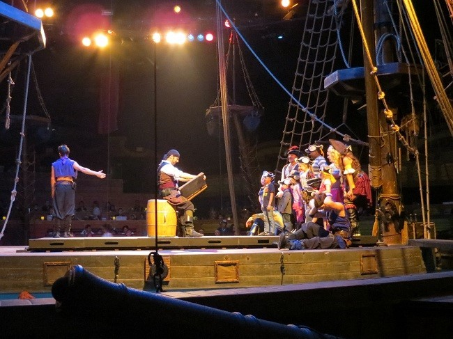 """They pulled the kids, and two adults from the audience and brought them aboard the ship. They were all sworn in as pirates! Now for the surprise, the male adult human, tricked the female adult human into dressing as a pirate wench and coming to the show with him. She thought she was going to a costume dinner I think. She seemed distraught being the only dinner attendee dressed as a pirate. We were wondering why he duped her like this, until now. They dismissed the children, then he got down on one knee and proposed to marry her. She started jumping in hysterics, the pirates translated for us and told us that she said yes.  It was so sweet, that even my eyes began to water. 20 years ago this coming Valentines day, I proposed to my wife, and she looked at me and said """"I'll think about it"""". I had to wait three days to get an answer, and I think you all probably know what her answer was. I have never regretted marrying Athena, I would do it all over again in less time than it takes for a heart beat to pass. I tried to get married that fast the first time, when I woman has to think about it, she has to think about it,  but you can take her decision to the bank. Guys listen up!  There is nothing like spectacular proposal to sweep your girl off her feet."""