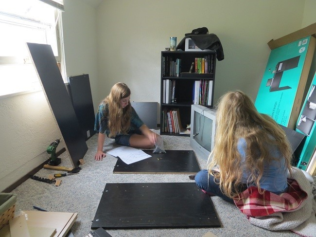 They got a desk kit. Holly and Sarah are beginning to assemble it