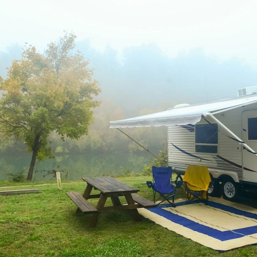 RV-with shade-and-table-while-misty-weather