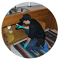 a redline pest control technician inspecting for rodents