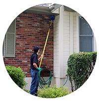a redline pest control technician de-webbing the outside of a home