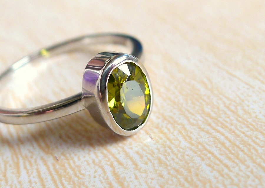Peridot in white gold. Peridot is one of the few gemtstones that occur in only one color: olive green.