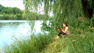 stock-footage-girl-reads-the-book-on-the-bank-of-river-1