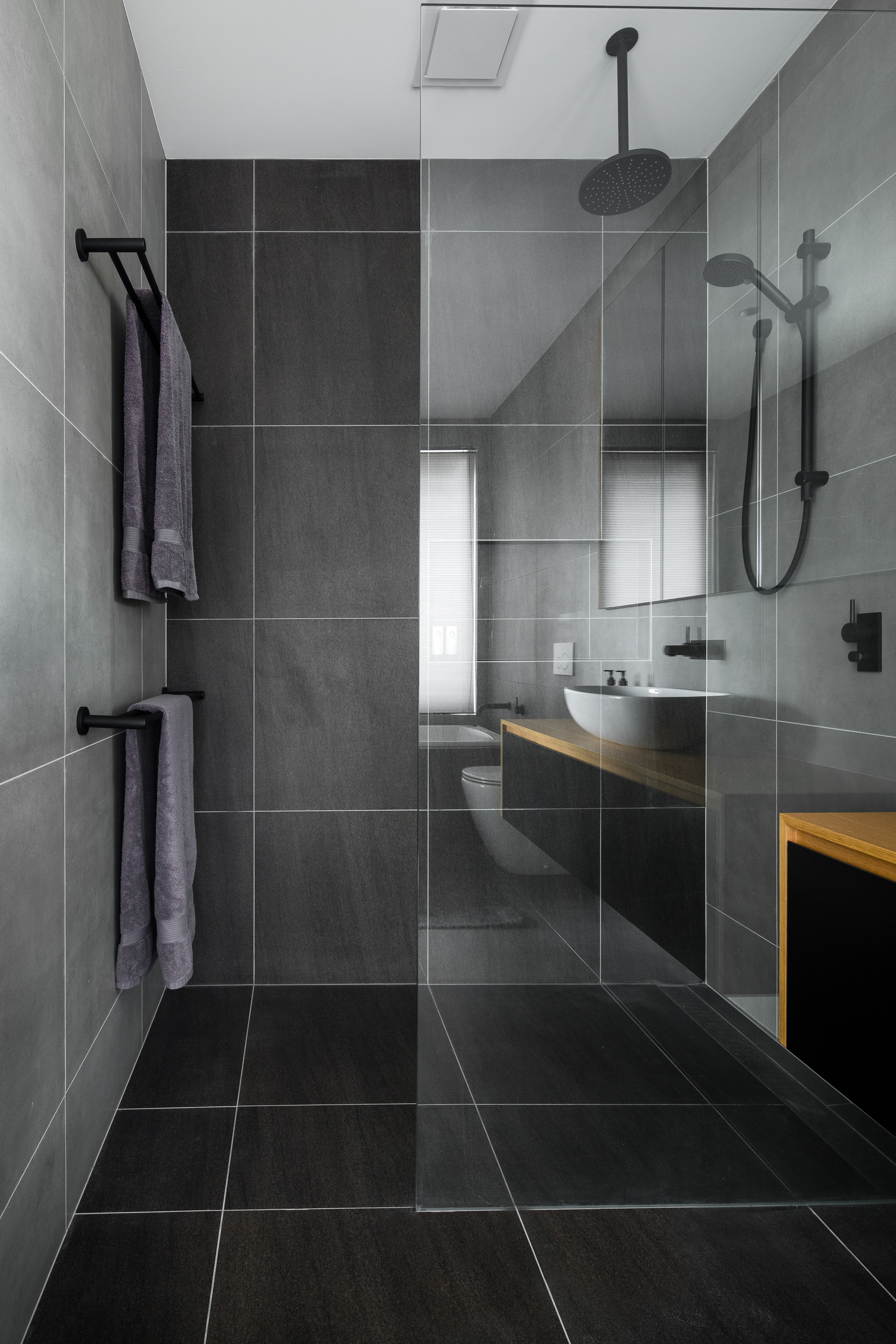 Modern dark grey tiled bathroom with glass shower screen and timber benchtop