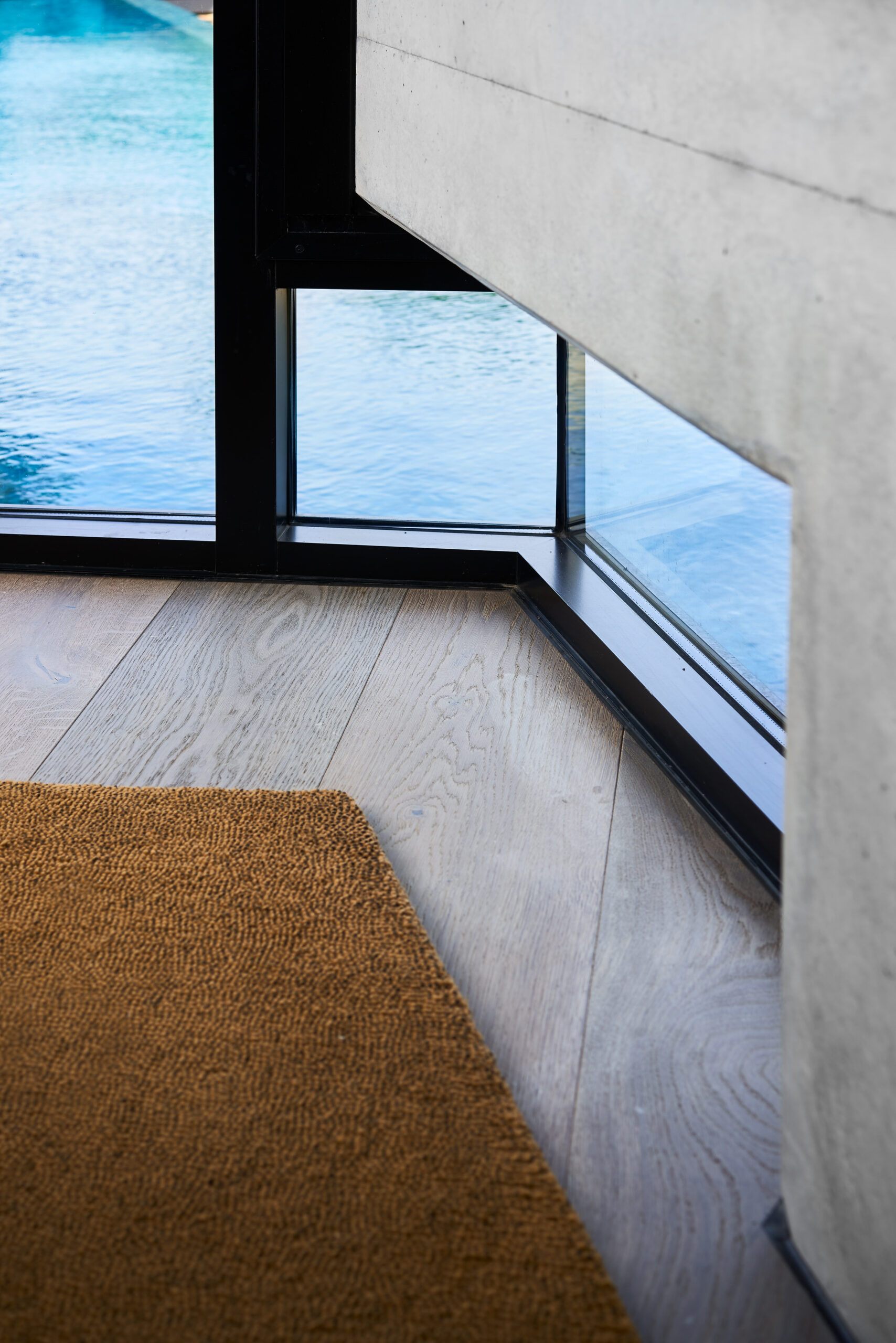 timber floor leading to a black aluminium window frame at floor level that reveals the pool below