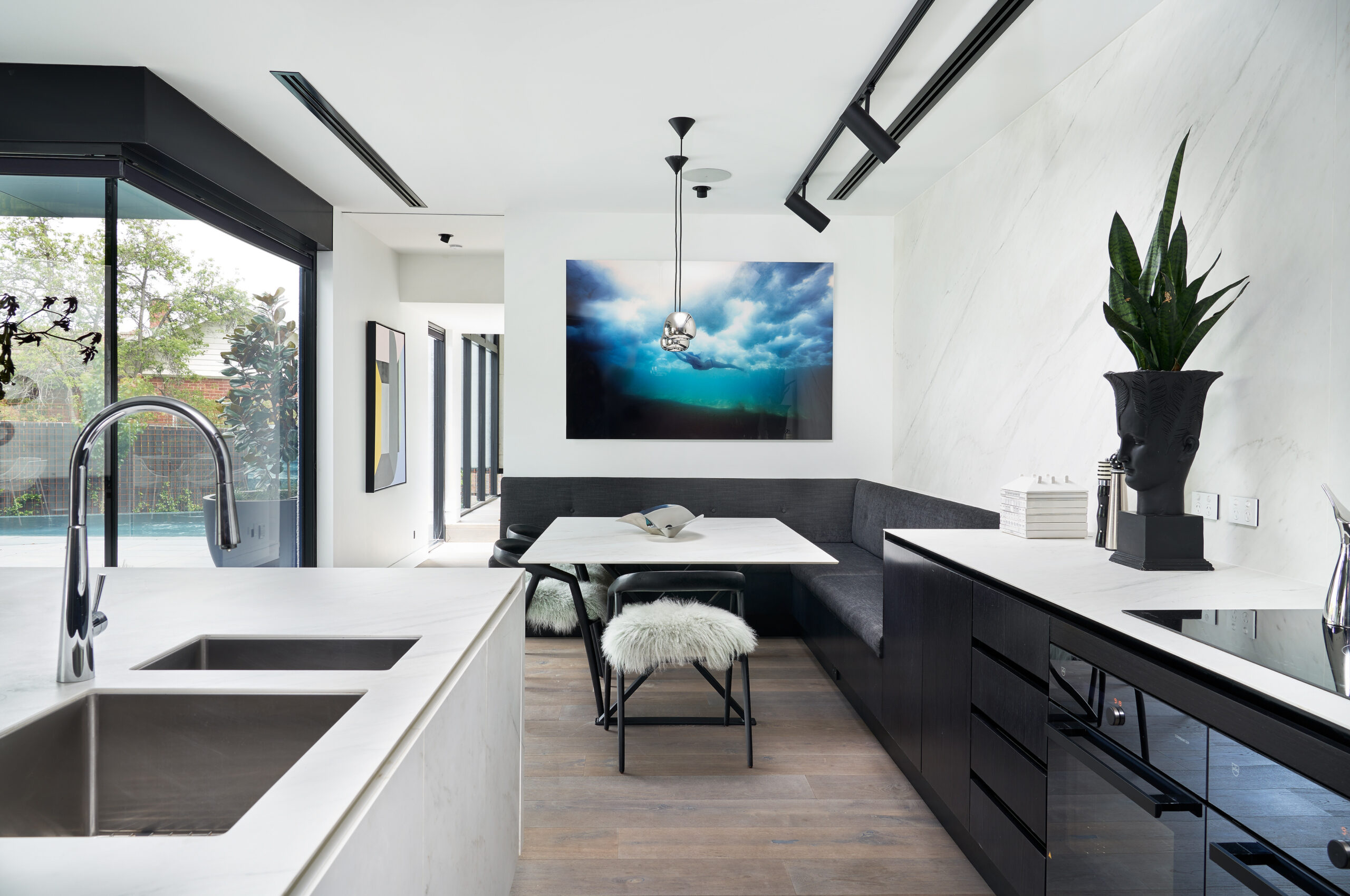 bright white modern open plan kitchen with meals area complete with bench seating