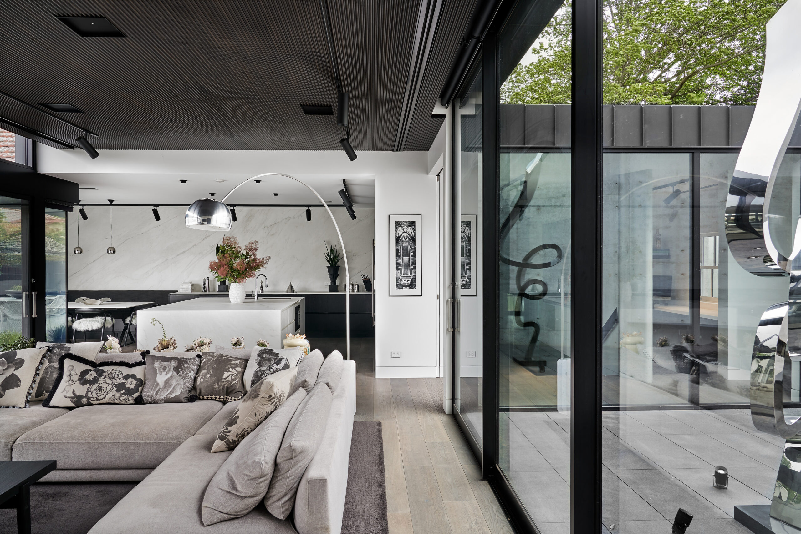 Open plan lounge area with huge glass sliding doors leading out to a private walled courtyard on one side and pool area on the other