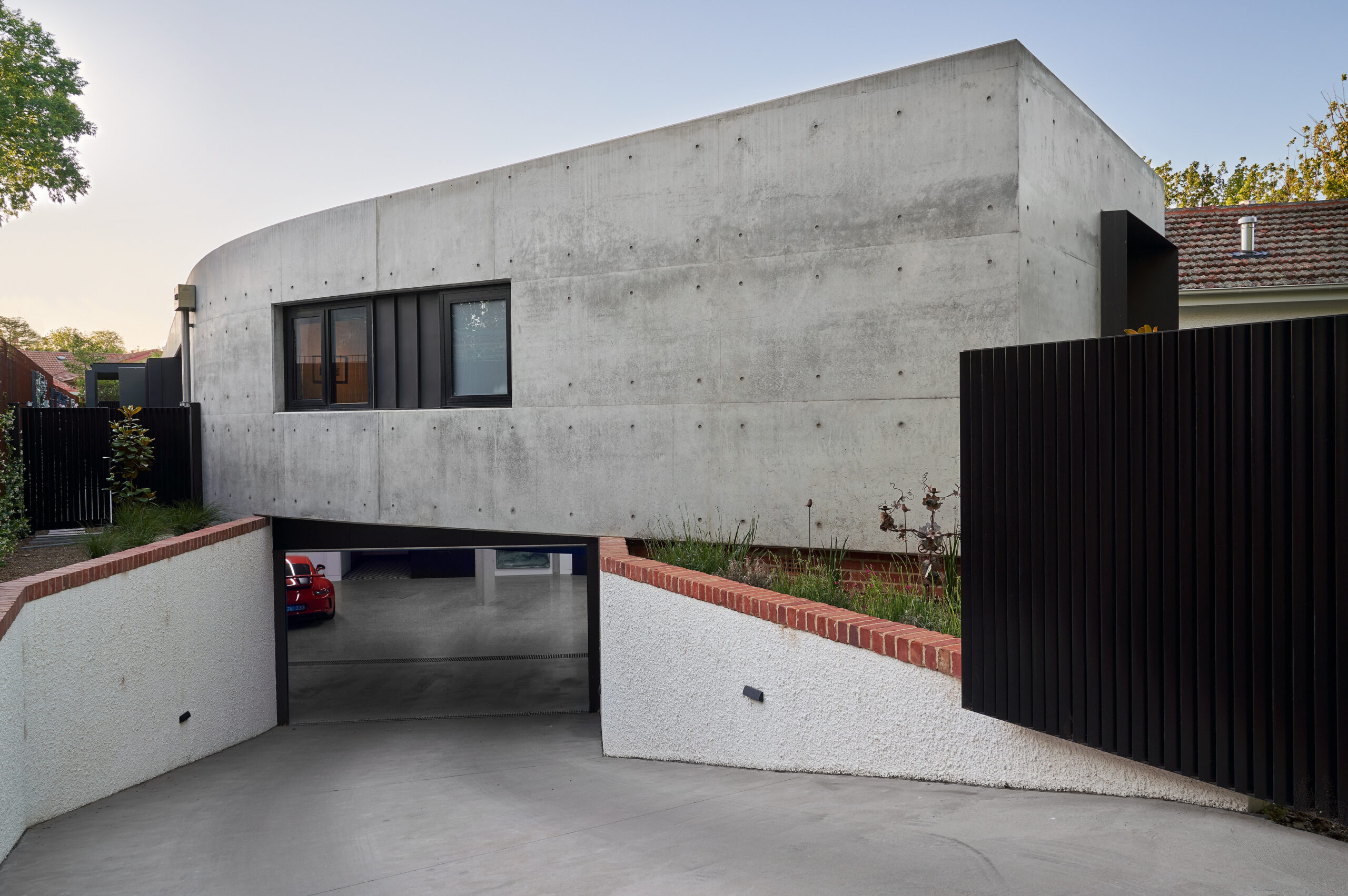 Underground garage positioned under sweeping curved off form concrete wall
