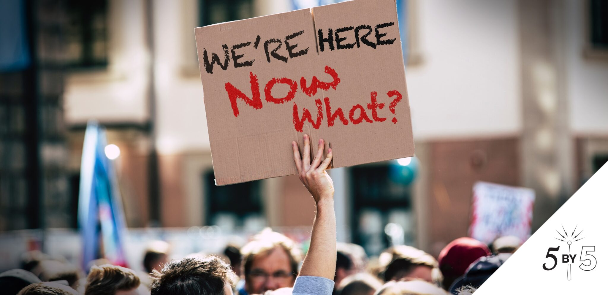 "man's arm above crowd holding sign ""We're Here. Now What?"""