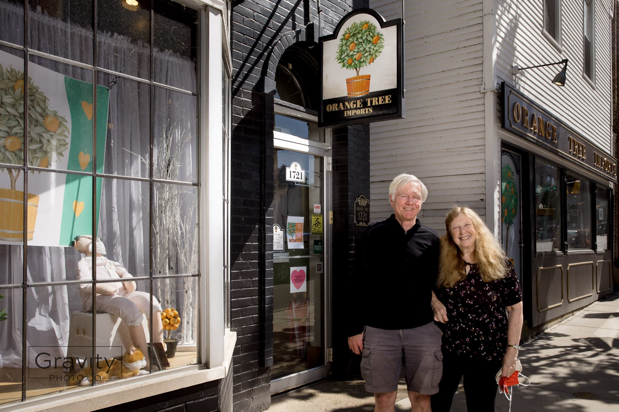 Carol and Dean Schroeder stand in front of their specialty retail shop, Orange Tree Imports.