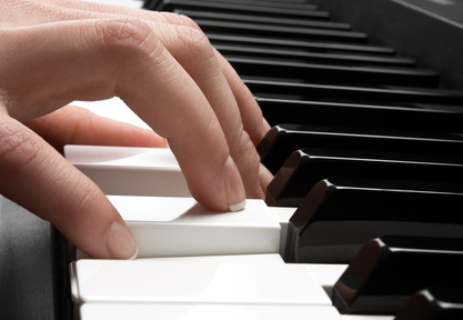 woman's hand playing the piano