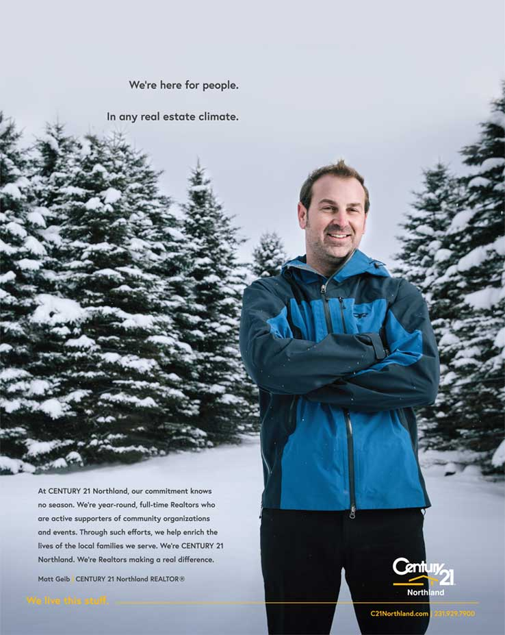 Man standing in snowy landscape with snow covered pine trees in background.