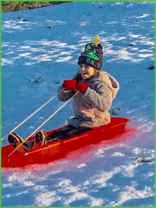 Girl Sledding at Grand View Campground and RV Park