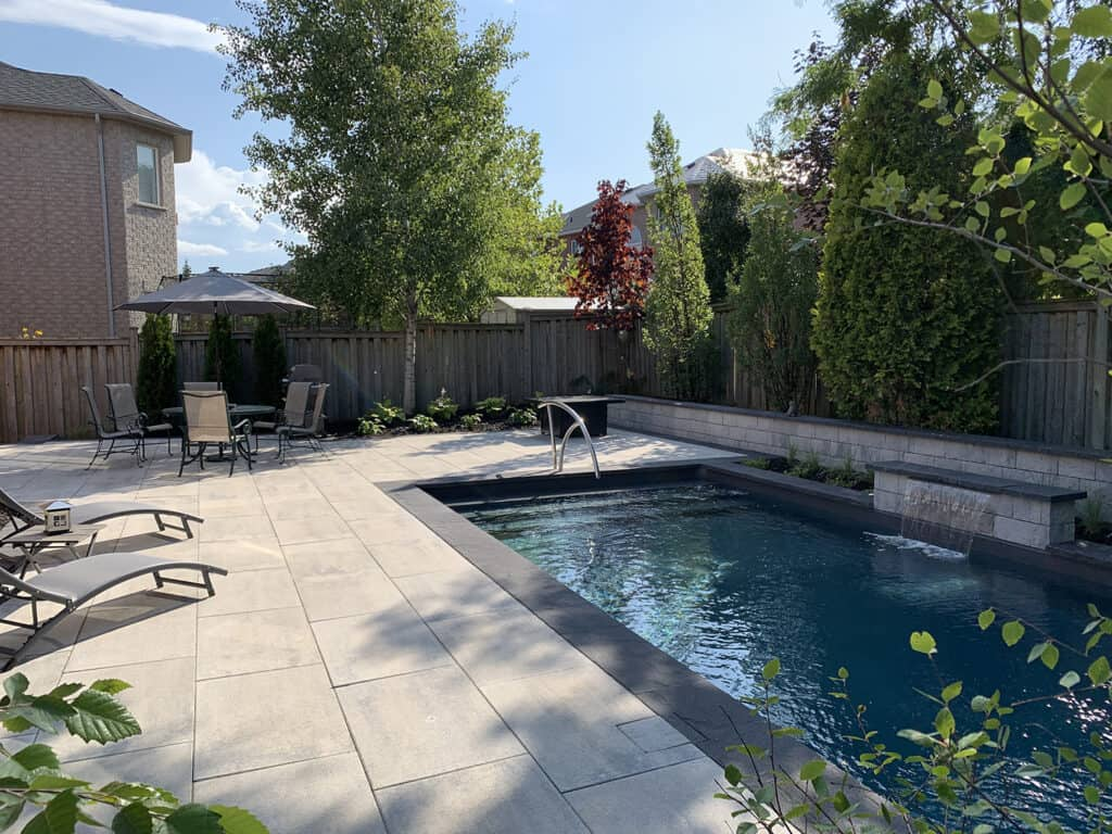 In ground pool, surrounded by a concrete patio and trees. Renovations and landscaping.