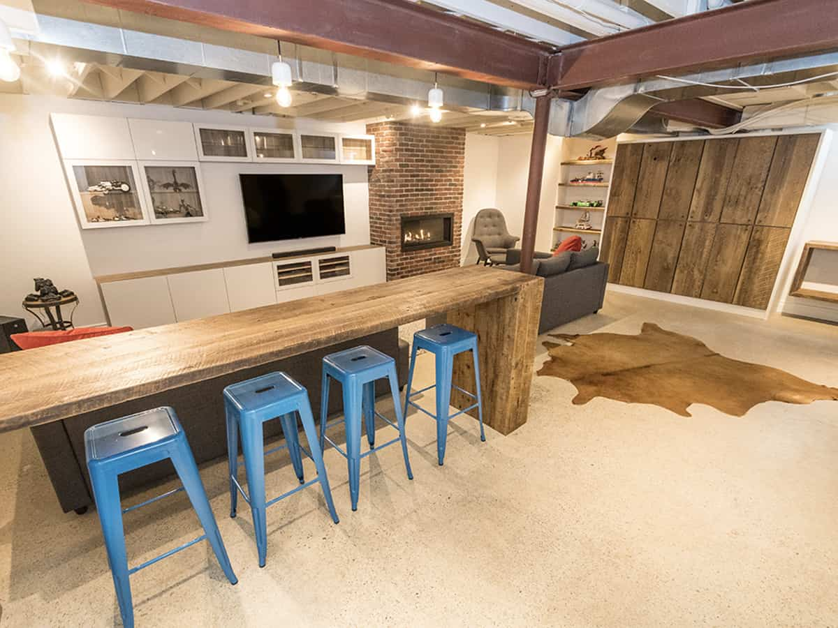 Basement with wooden table and blue stools.