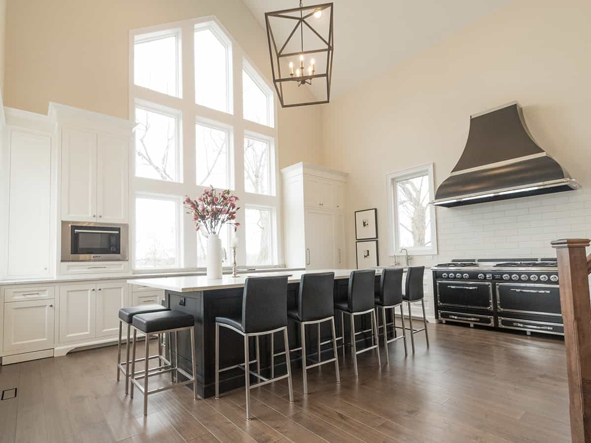 Kitchen with a big island and black stools.
