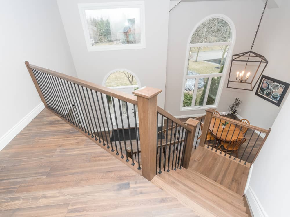 Light brown staircase leading down to a kitchen.