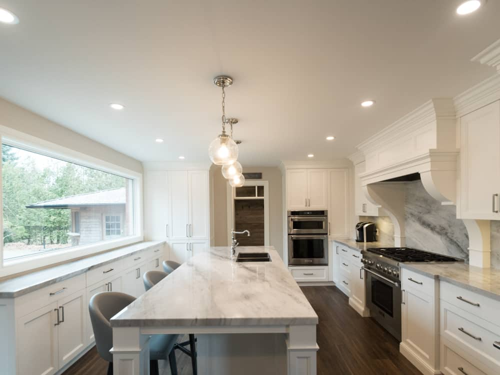Modern kitchen with stainless steel gas-top stove and marble island.