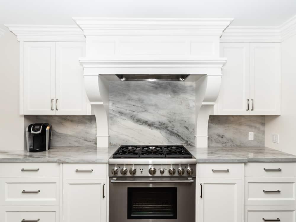 Marble backsplash behind a stainless steel gas top stove.