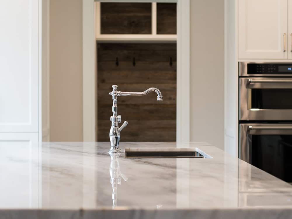 Marble countertops, with a sterling silver faucet.