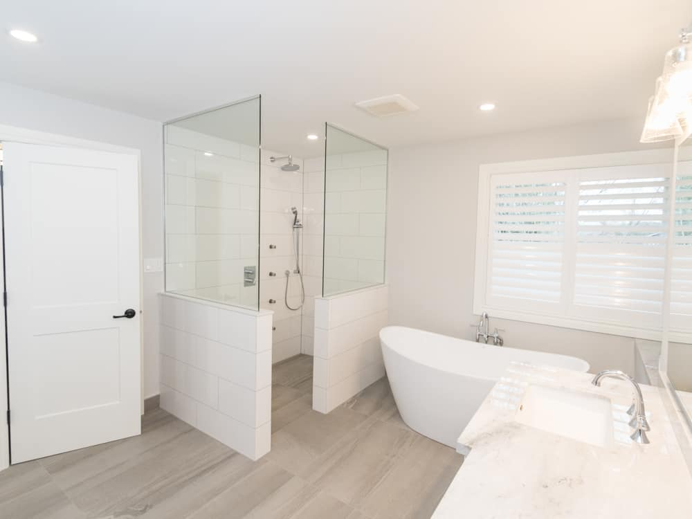 All white bathroom, with a glassed in shower.