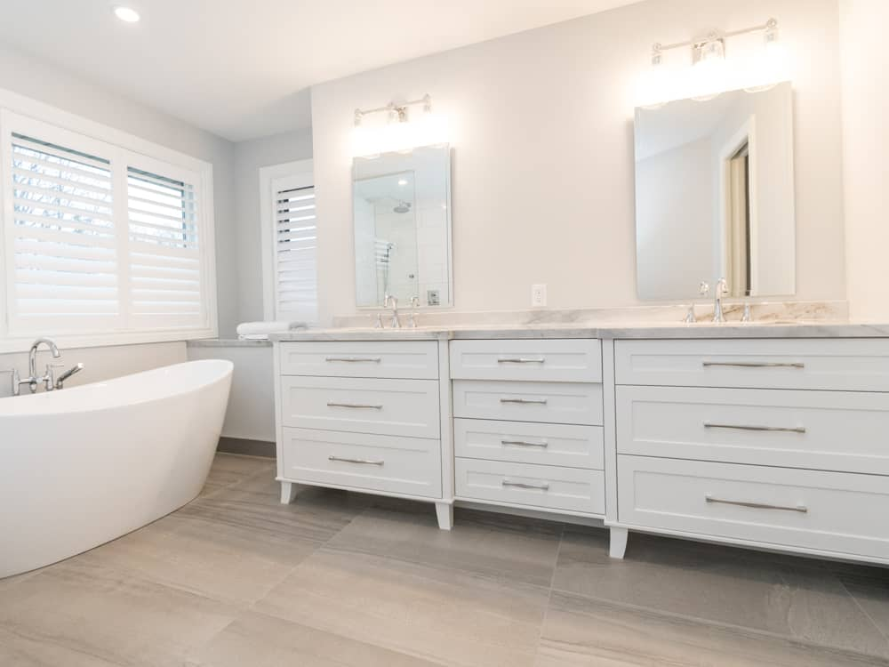 Double sink white vanity with two mirrors, next to a deep bath tub.