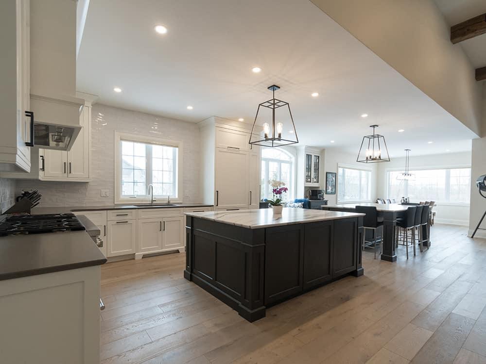 Kitchen with dark island and white cupboards