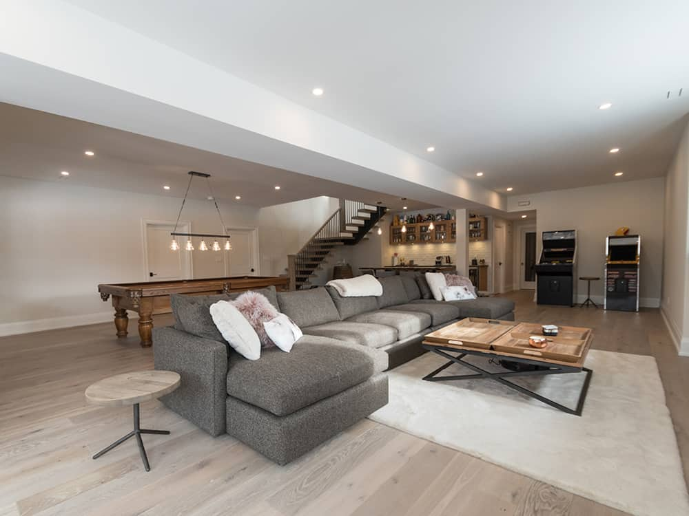 Basement area with grey couch.