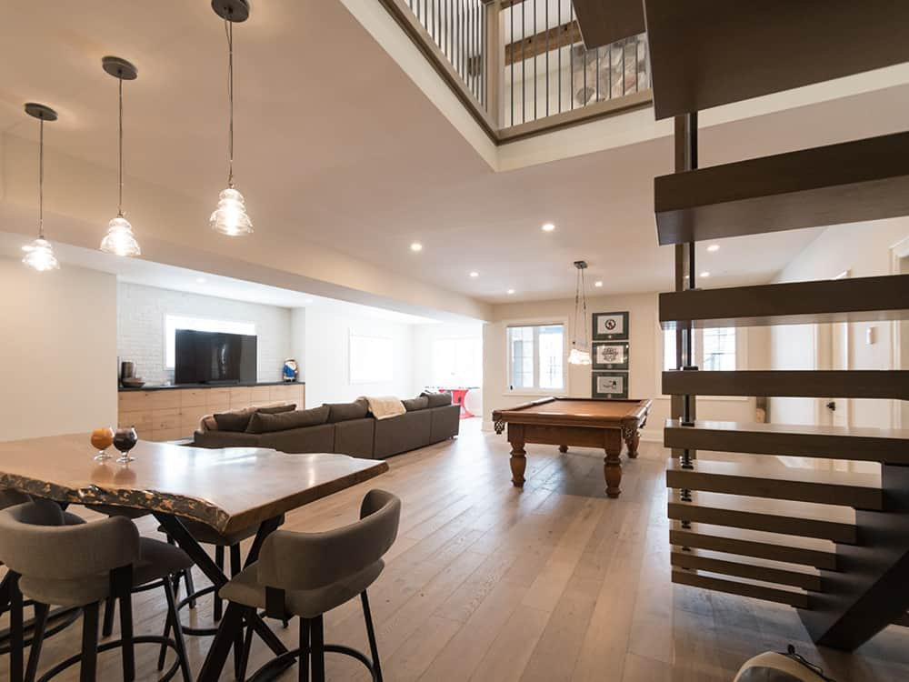 Basement area with grey couch, dark staircase and long wooden table.