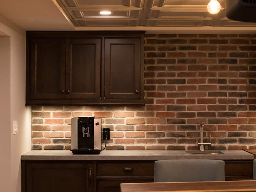 Brick bar area, with dark cupboards.