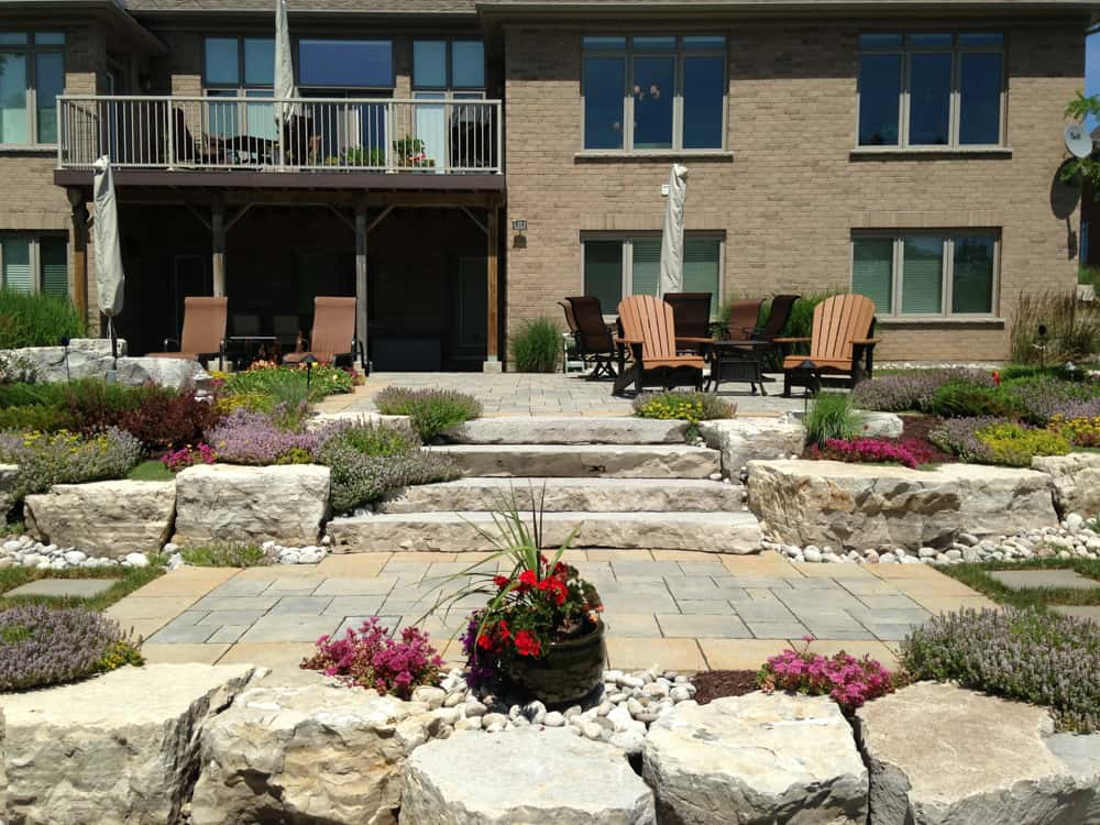 Stone backyard with steps and chairs, and a garden built in.