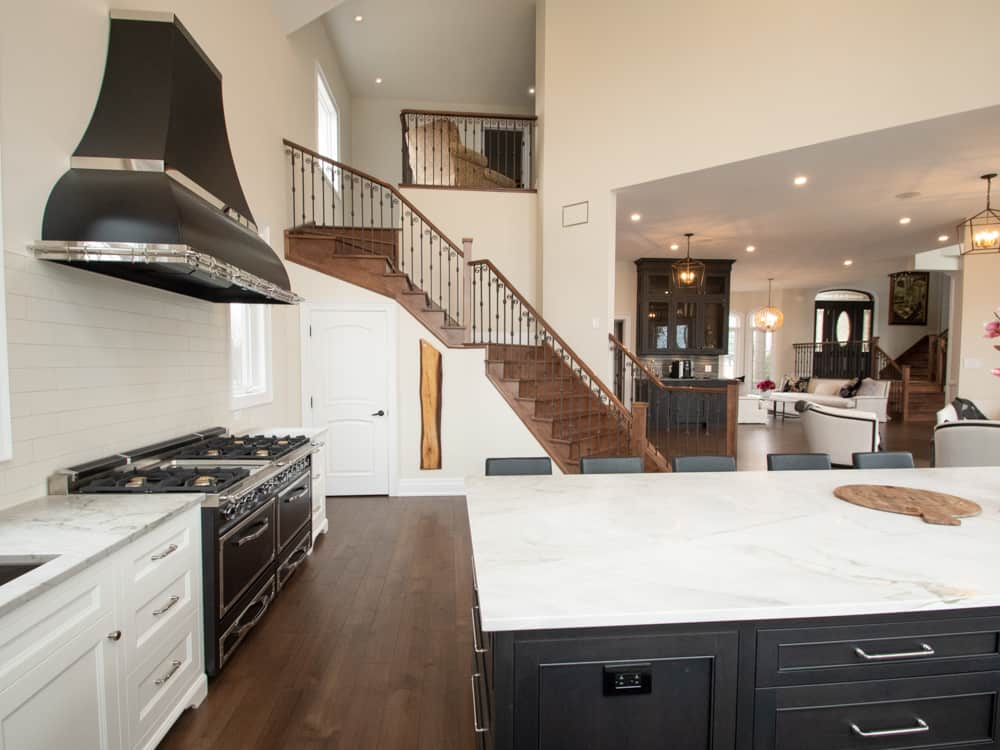 White countertop kitchen with dark cupboards, open concept to living space and stairway.