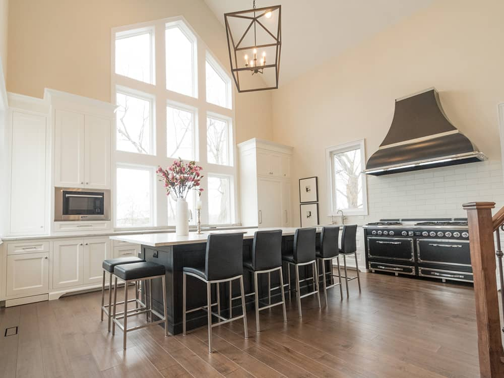 Modern kitchen with black stools, island and a black gas top stove and oven.